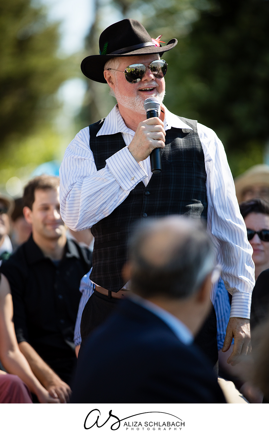 Photo of a man in a had with sunglasses speaking into a microphone at a wedding ceremony