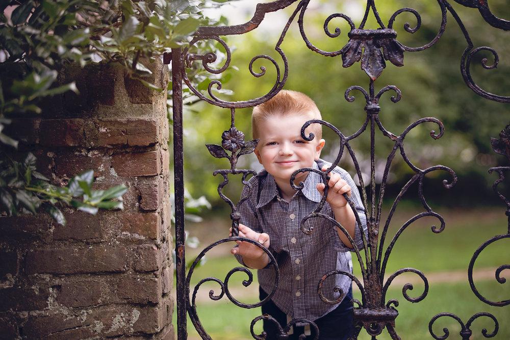 Little boy peering through a wraught iron gate at Appleford Estate in Villanova