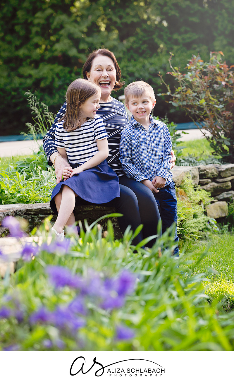Family photograph of a laughing grandma with her grandaughter and grandson by the flowers