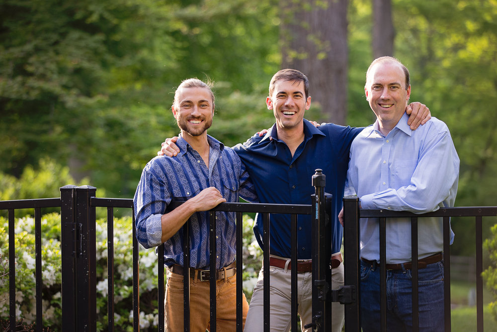 Outdoor portrait of three smiling grown brothers leaning on a fence