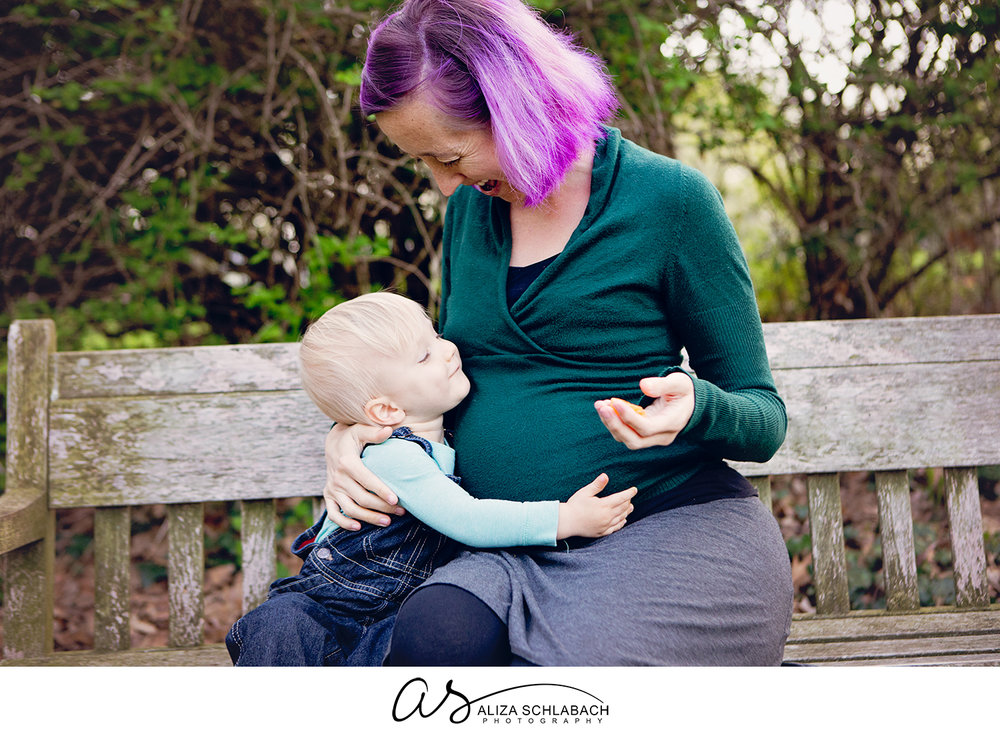 Photo of a pregnant woman with purple hair and her little boy holding her tummy on a bench