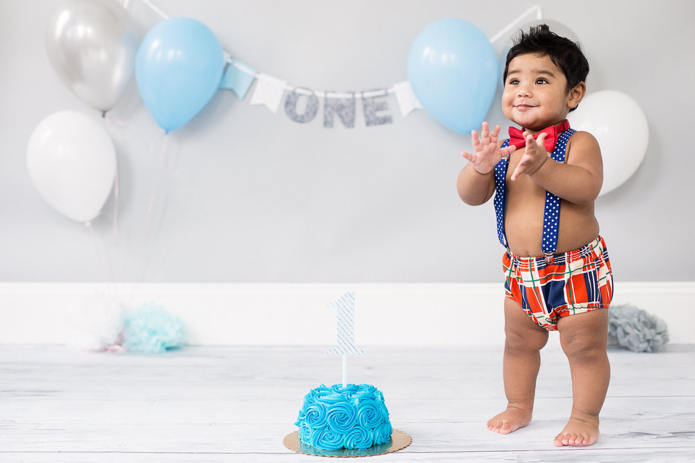 1 year old boy clapping at his cake smash photo shoot