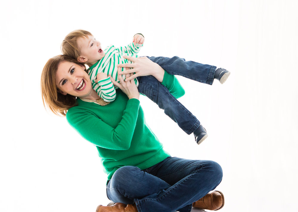 Backlit photo of a woman in a green sweater swinger a little toddler into the air