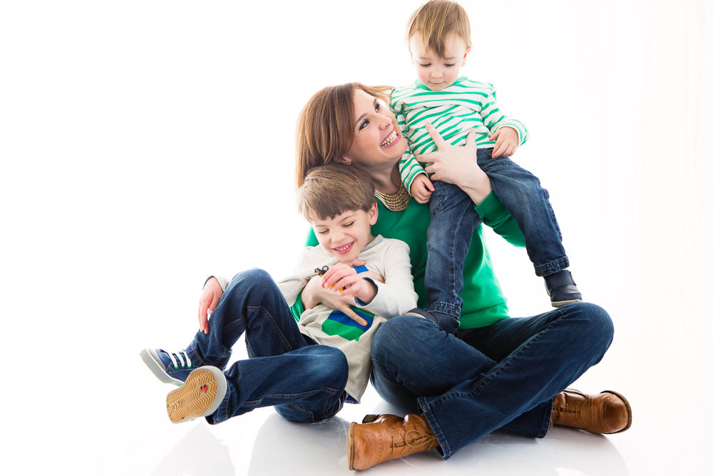 Backlit photo of a woman and two little boys, green and blue and white color scheme