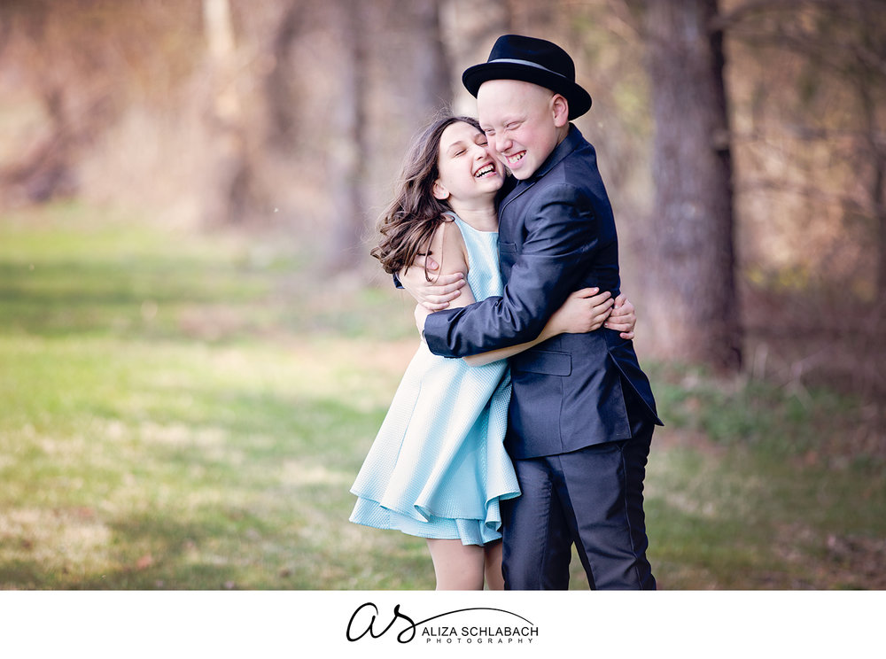 Outdoor portrait of brother and sister hugging