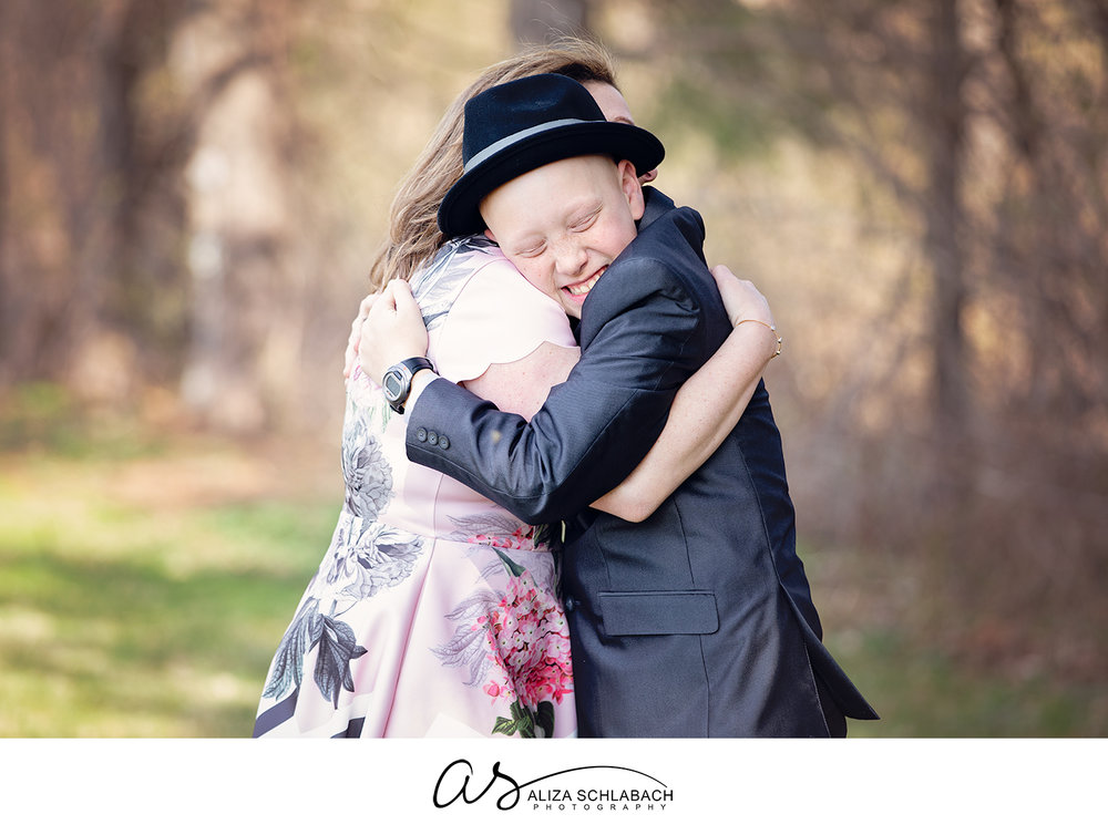 Outdoor photo of a boy in a suit hugging his mom