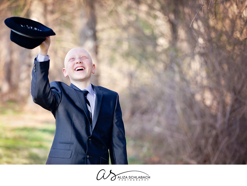 Outdoor portrait of boy in a suit with alopecia universalis smiling and waving his hat