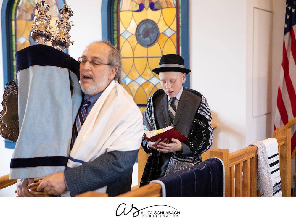 Photo of rabbi carrying torah while bar mitzvah boy follows singing