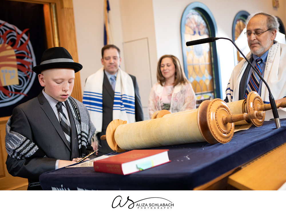 Photo of Bar Mitzvah boy with Rabbi and parents in the background