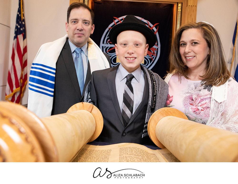 Portrait of Bar Mitzvah boy with his parents at the Torah