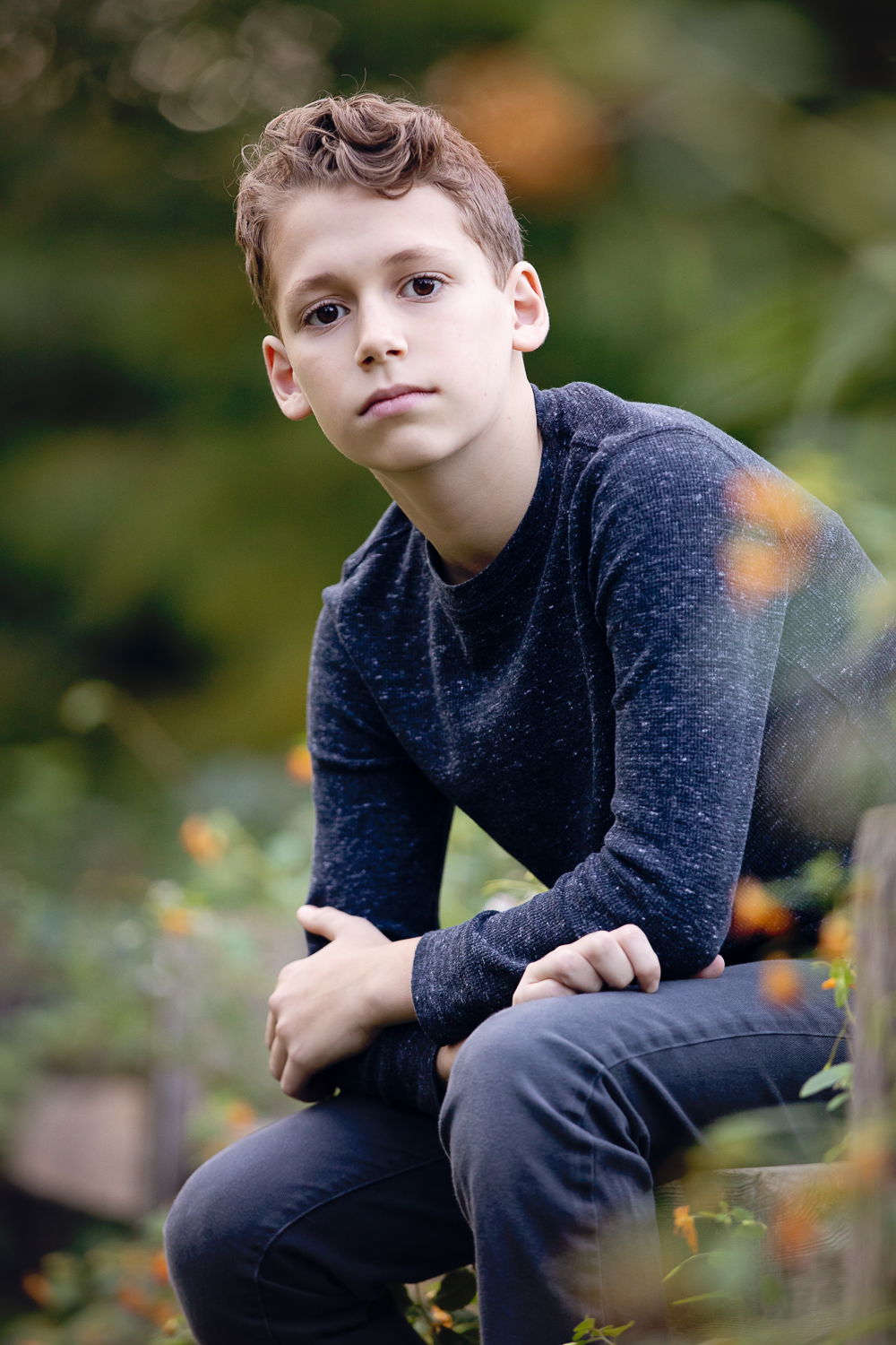 Preteen boy looking cool sitting on a fence