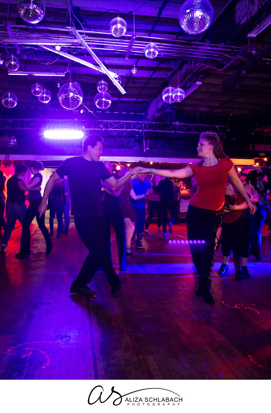 Photograph of partner dancing under disco balls