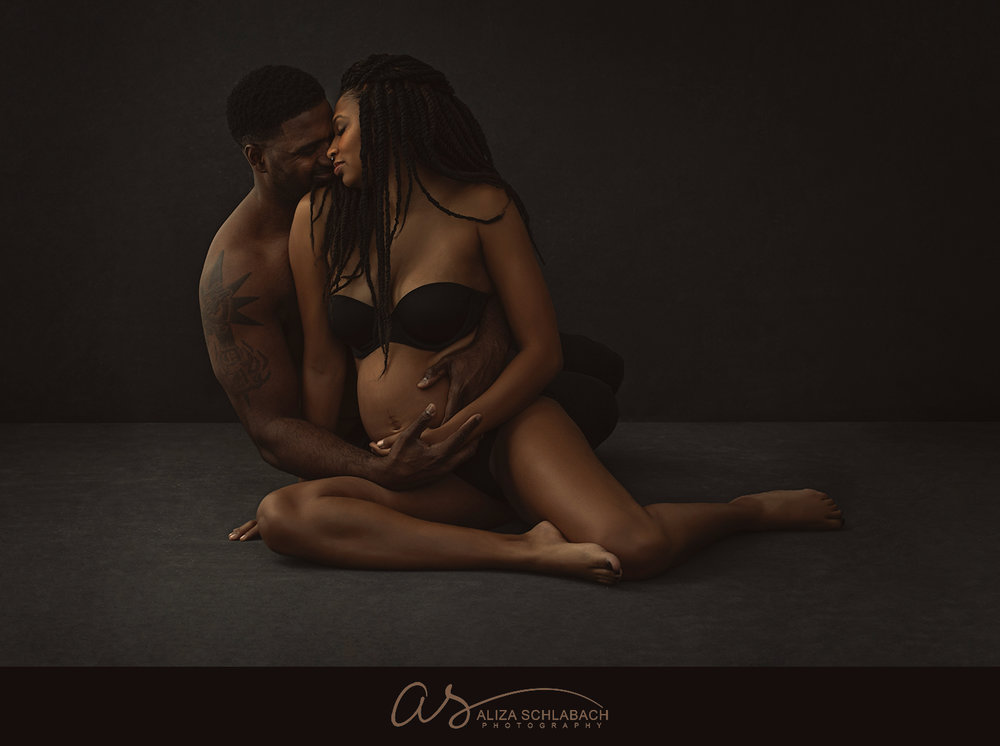 Seated maternity portrait of stunning black couple