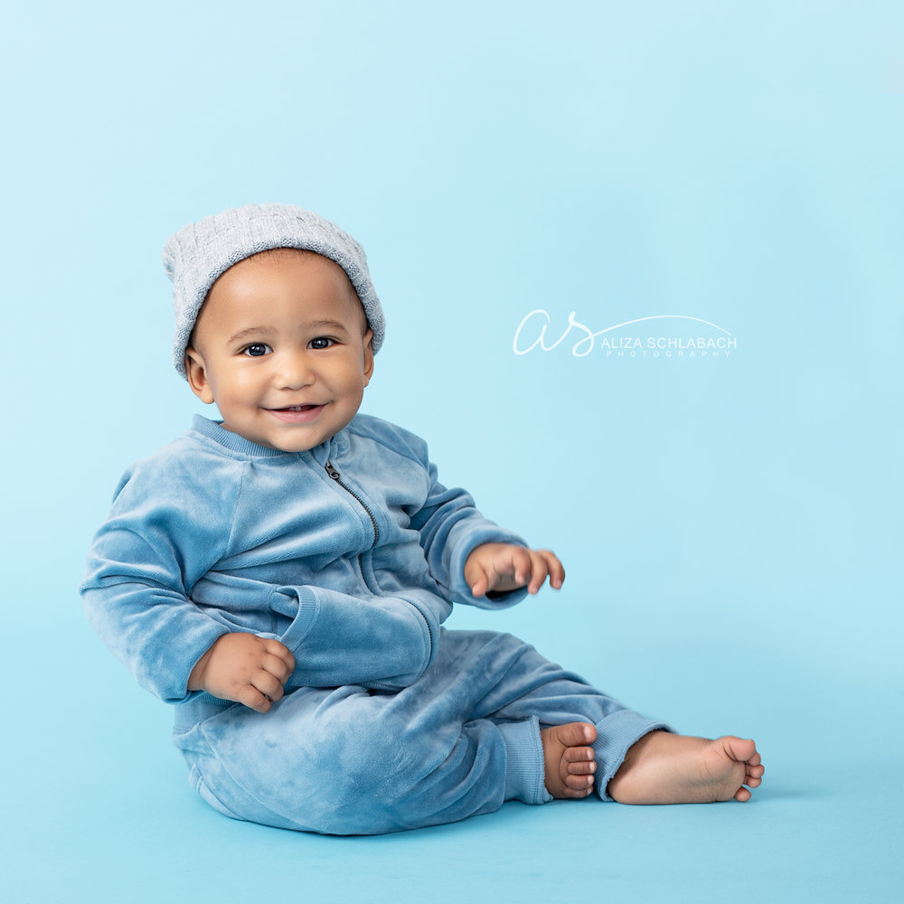 Photo of a cute smiling black baby in a hat and tracksuit on a blue background