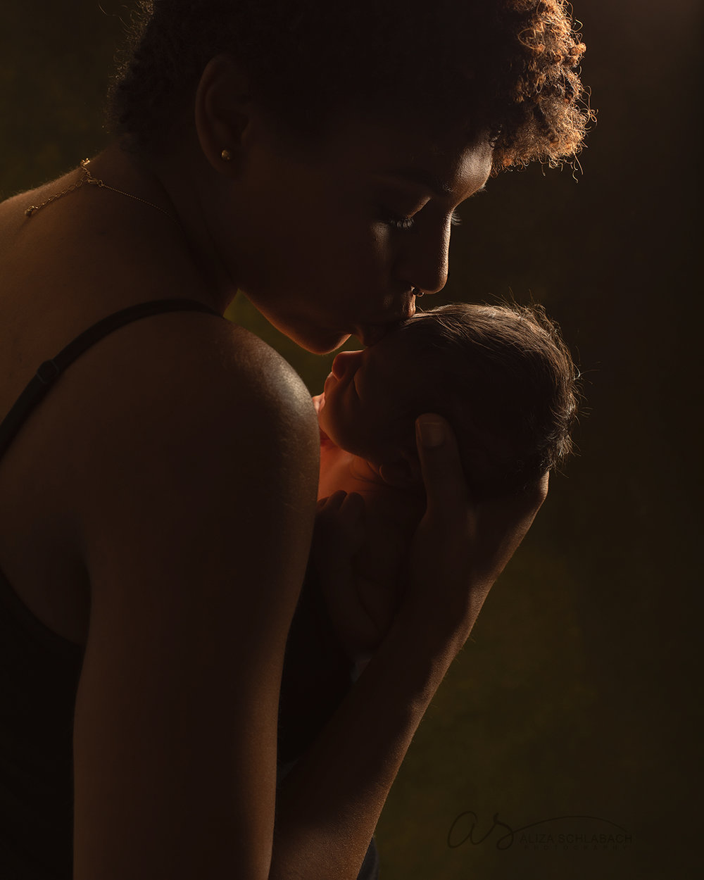 Silhouette of mother kissing her newborn daughter