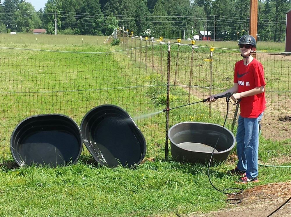 GATE student pressure washing troughs at the ranch, Summer 2015