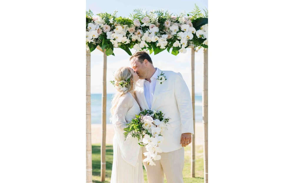 Bride and Groom Kissing Under Ceremony Arch
