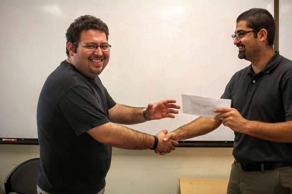 Juan Zepeda, one of the Four Ingenieros Founder, handing over the check to Miguel Lopez, SHPE Ingenium President, for the sponsorship of the Four Ingenieros Engineering Competition.
