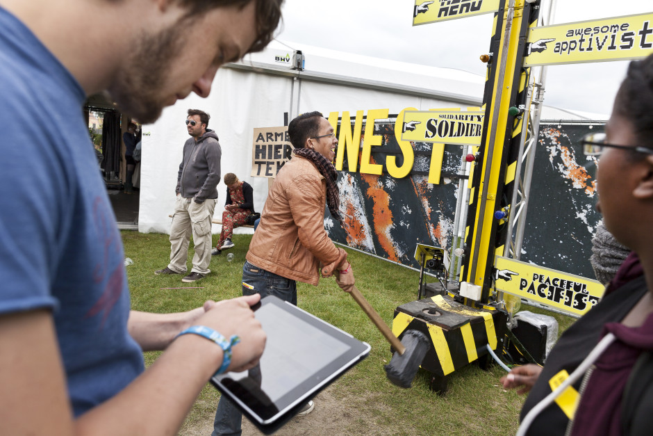 A member of the Amnesty International team takes a festival goer's email address while another participant gets ready to try his luck with the Kop van Jut.