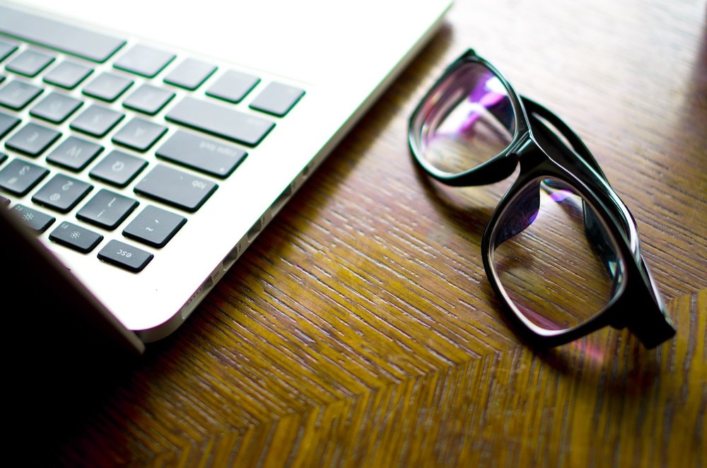 computer glasses next to macbook