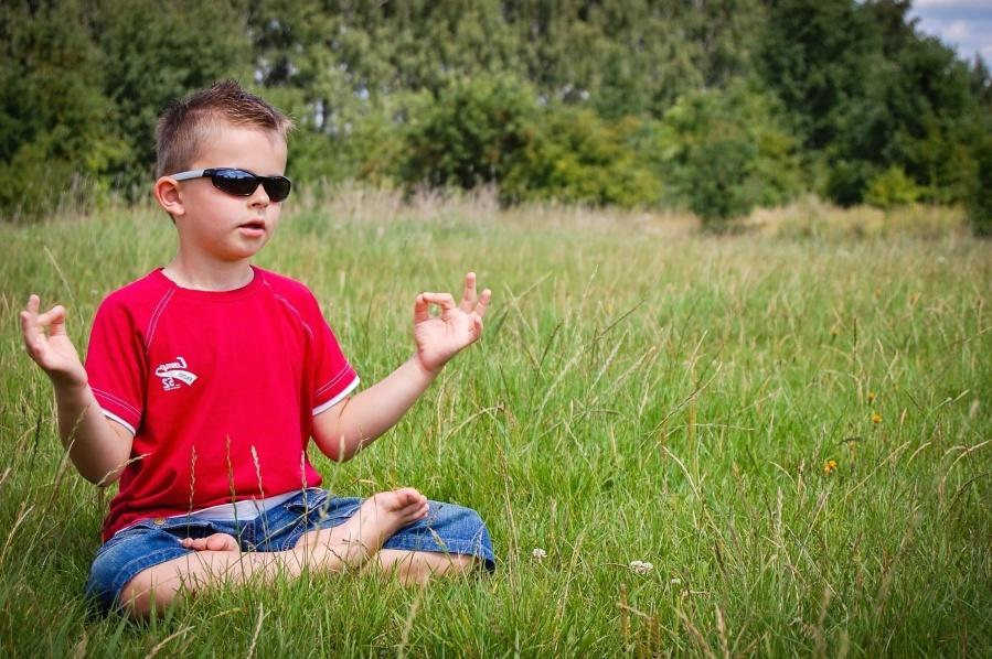 Little boy wearing sports sunglasses and meditating