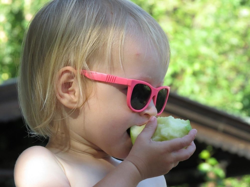 little girl wearing sunglasses eating apple