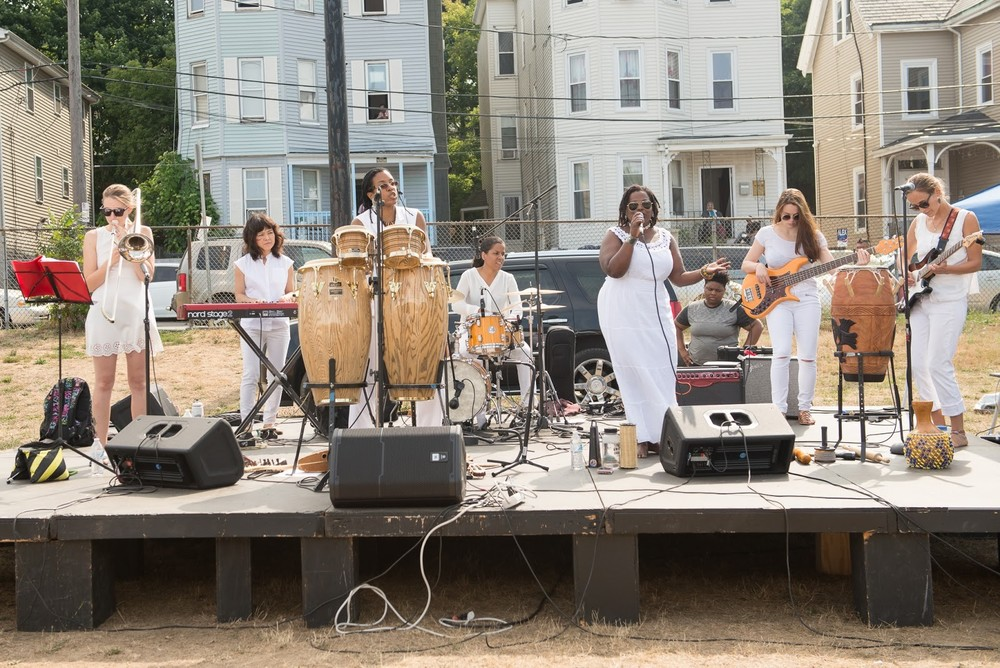 Zili Misik, a multi-ethnic all female band, lead by Kera Washington, perform at DSNI's 28th Annual Multicultural Festival. Image shows 7 women dressed all in white singing and playing trumpet, keyboard, drum kit, bongos, guitar, and bass, on a platform at Mary Hannon Park in Dorchester. Photography by Mark Fusco.