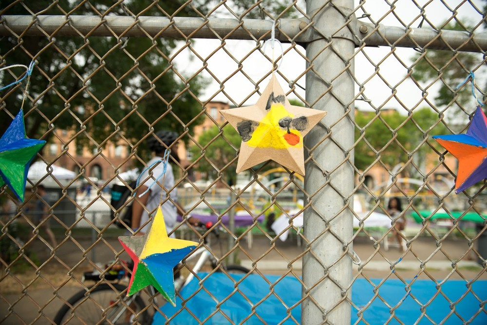 DSNI Art Wall display at 28th Annual Multicultural Festival. Image shows 4 decorated cardboard stars hanging on a chain link fence, centered is one decorated with a yellow bird. Photography by Mark Fusco.