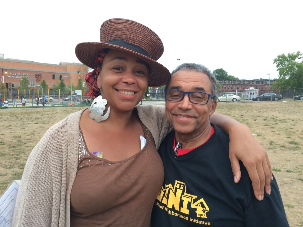 DSNI's fearless leaders, Ramona Lisa Alexander and Jose Barros, at the 28th Annual Multicultural Festival. Image shows Ramona, in a brown straw top hat, and Jose, in a DSNI T-Shirt and his blue framed glasses, at Mary Hannon Park in Dorchester. Photography by Ros Everdell.