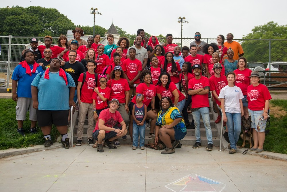 DSNI Summer Youth Organizers, Staff, and volunteers celebrate a successful 28th Annual Multicultural Festival. Image shows about 50 people, most in red T-Shirts, and a German Shepherd at Mary Hannon Park in Dorchester. Photography by Mark Fusco.
