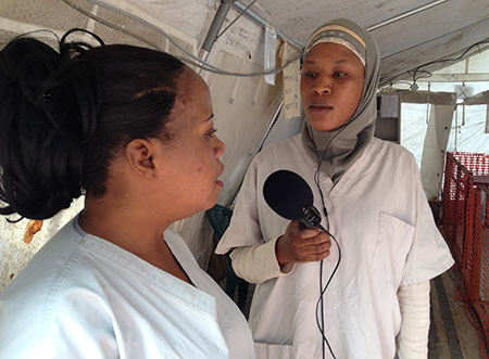 Ebola Chrono reporter Asmaou Diallo interviews a health care worker from inside the Donka Ebola treatment center in Conakry. ( credit : Pierre Mignault/Internews)