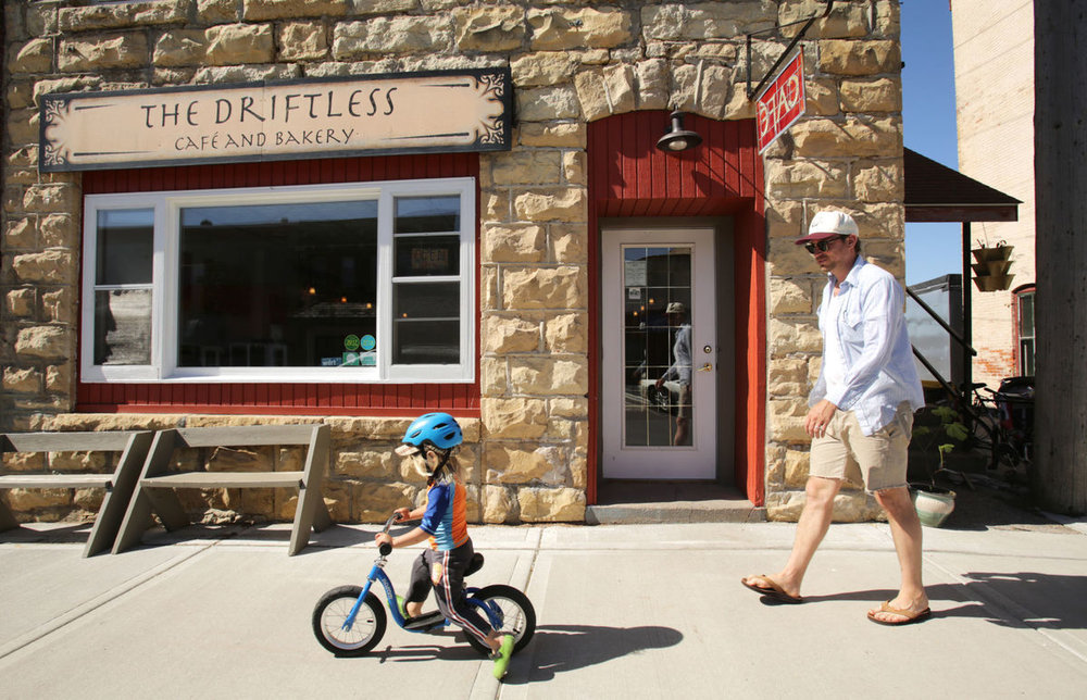 Eric Hartwig and his son, Ernest, 3, pass Driftless Cafe during an afternoon walk in Viroqua.  Photo by Amber Arnold, State Journal