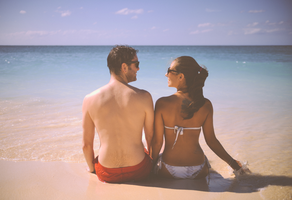 Cute Man And Woman Sitting On A Beach With Sea.jpg