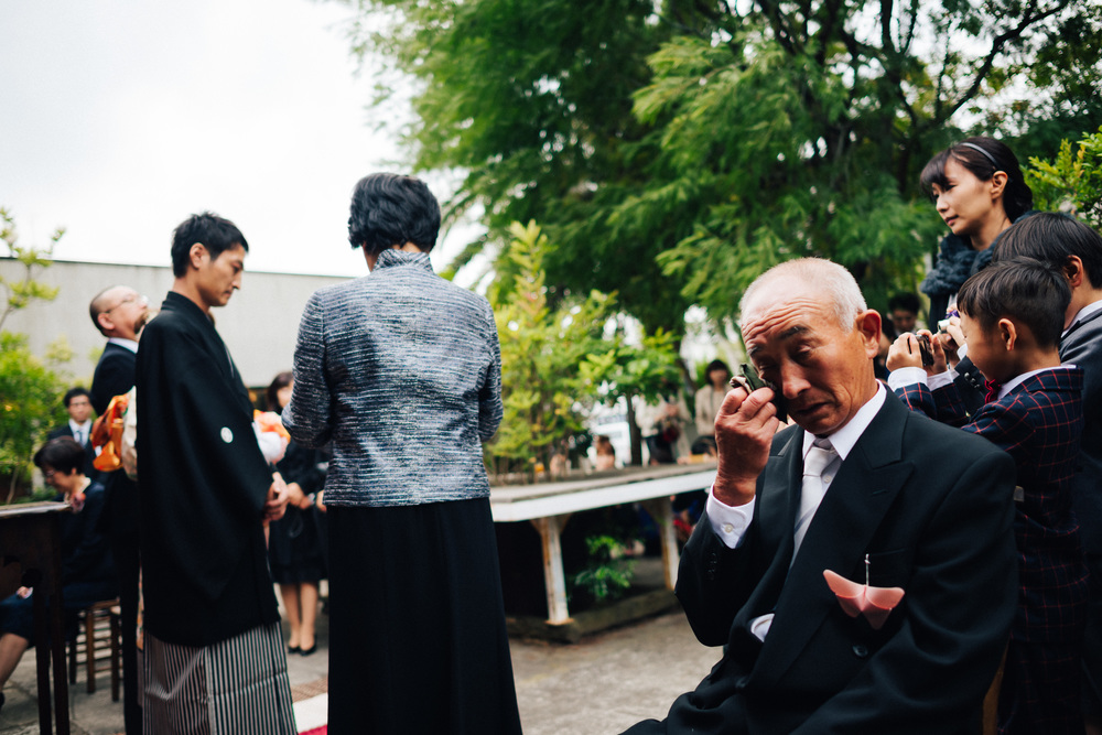挙式中の一コマ。新郎のお母さんが新郎への手紙を読んでいると、その過去の思い出話を聞いた新郎のお父さんがひっそりと涙を流していた。