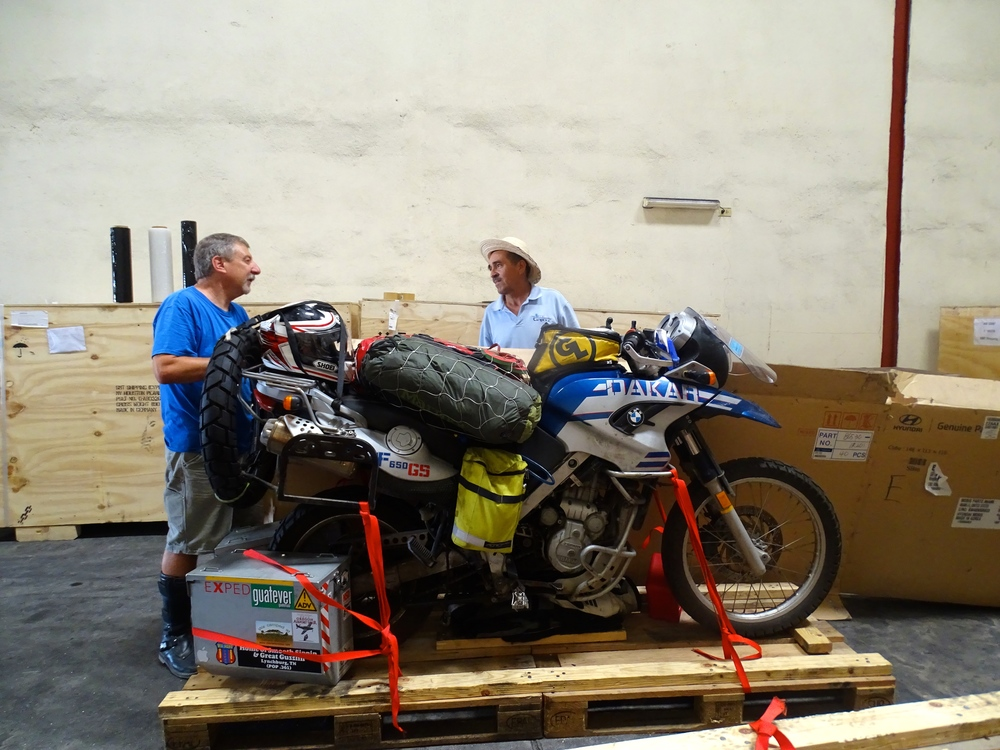Bike strapped down, boxes and other stuff packed in around the bike on the pallet.