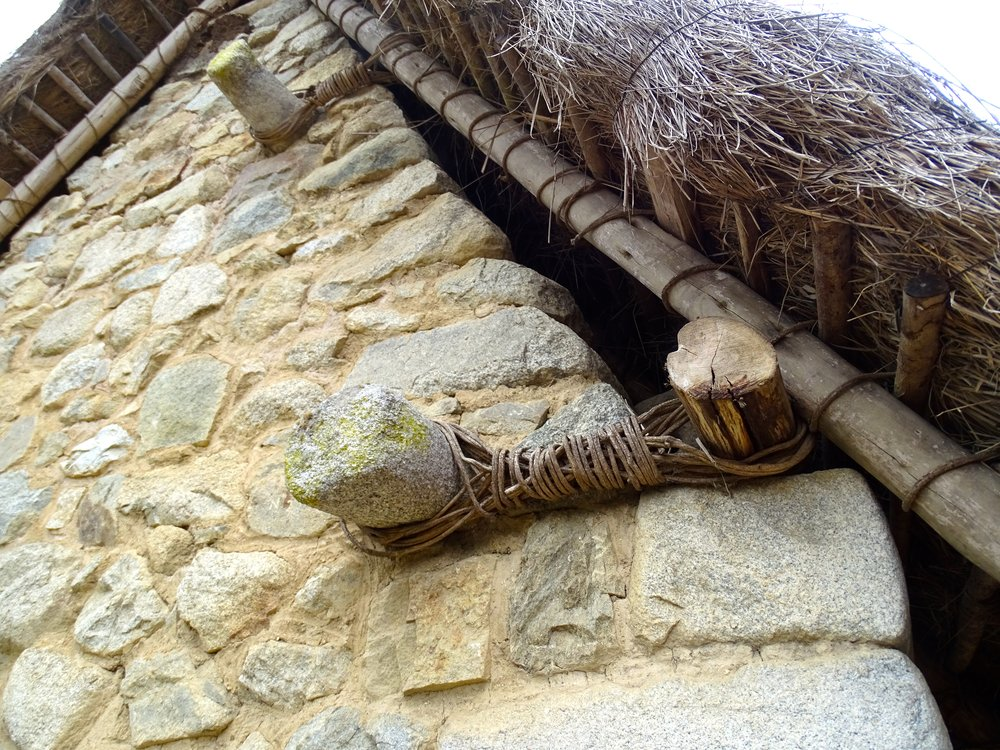 How to attach a wood and thatch roof to a stone gable wall.