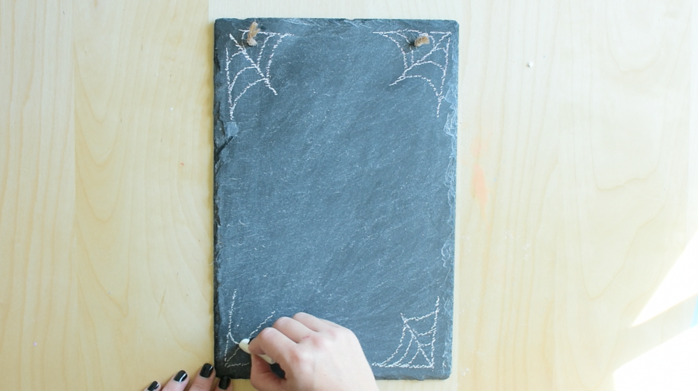In all 4 corners of the chalkboard draw spider webs