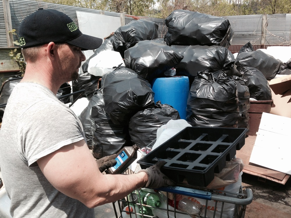 "Scott Ludolph separates plastics brought to his recycling yard. He allows customers to ""single source,"" meaning they may collect different materials, such as glass, cans and plastics, in a single bag."