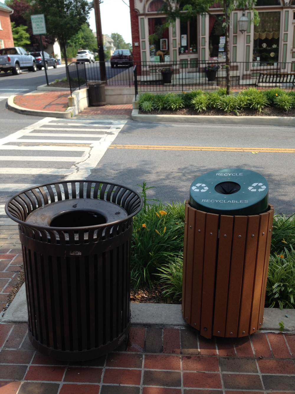 Recycling bins are paired with trash cans all along German Street.
