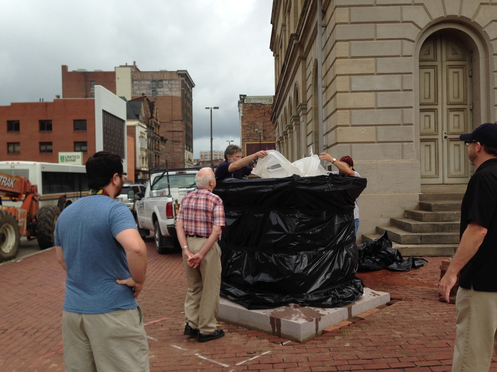 Workers remove the covering from the pedestal.