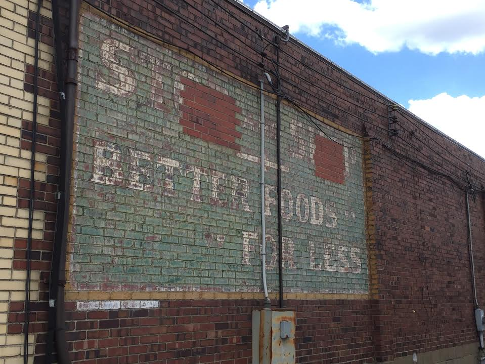"""Not all ghost signs are found at the top of buildings. Some are at ground level, like this one tucked away in a Valley View alley advertising """"better foods for less"""" at a defunct grocery."""