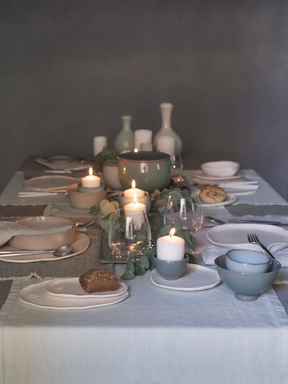 Tessuti morbidi dai colori tenui, bellissime ceramiche realizzate a mano, posti tavola tutti diversi e qualche ramo di eucalipto: un'eleganza naturale per una tavola in cui ogni oggetto racconta la sua storia.