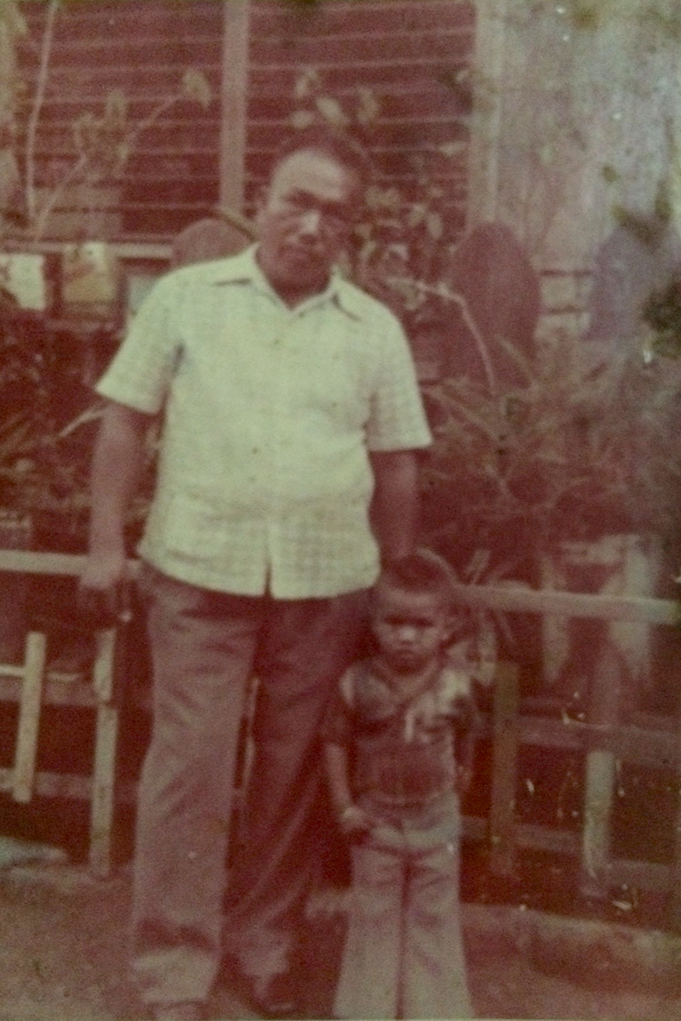 The author's Lolo — who brought the family to Tondo — and her kuya, in front of their old house in Gagalangin.