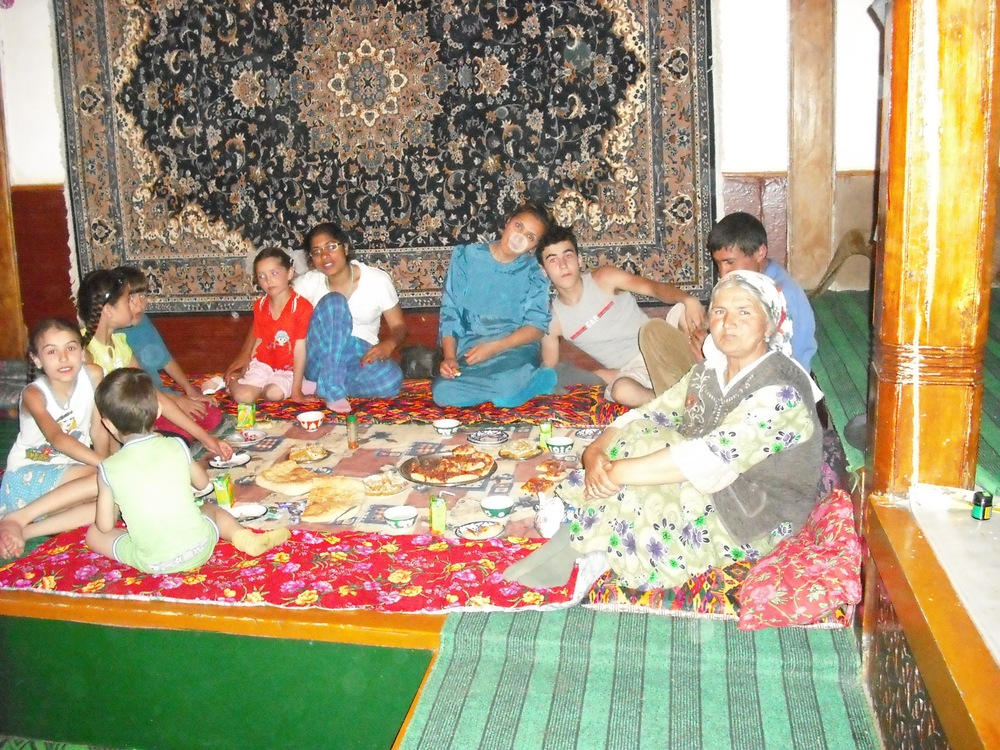 Dr. Shirinbek's family sit around a traditional dastarkhon (tablecloth) in his home.  It is his nephew's birthday, so there are special treats for all!