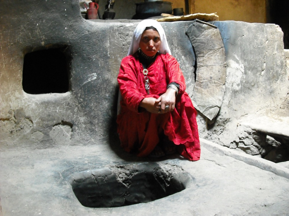 This Afghan Ismaili woman is sitting beside a traditional hearth.  Its  fire would both warm the house and be used to cook food.  Cooking over a fire is difficult and can be dangerous.  A number of development initiatives in both Tajikistan and Afghanistan have helped to bring electricity to the villages, enabling families to cook on modern stoves and use electric heaters.