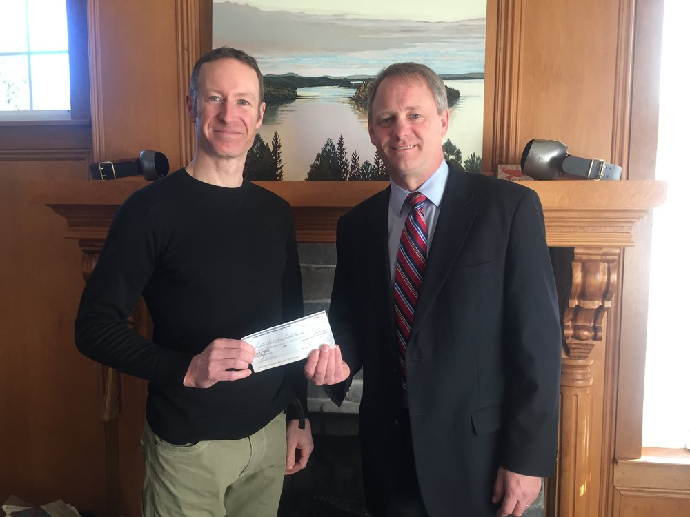 Dr Neil Manson presents the donation cheque to Bill MacMackin of the Greater Saint John Field House Project.