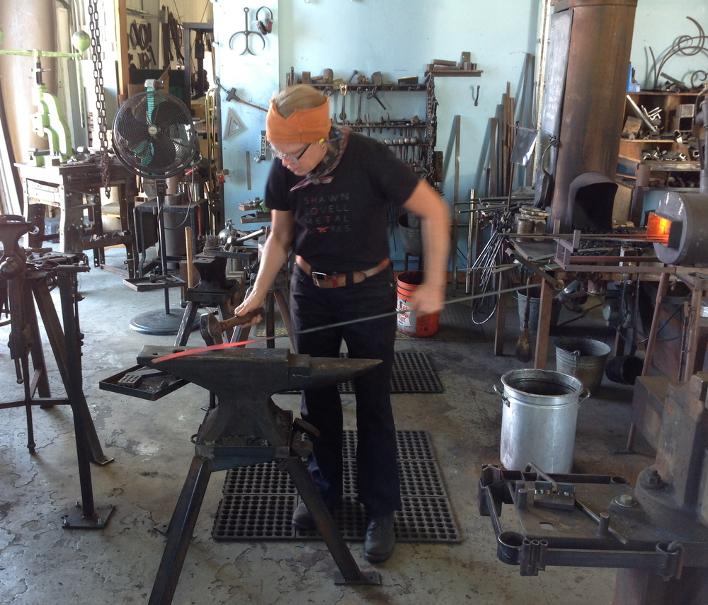 Blacksmith Shawn Lovell heating and shaping steel rods for Stellar Light elliptical frame, 2014-2015
