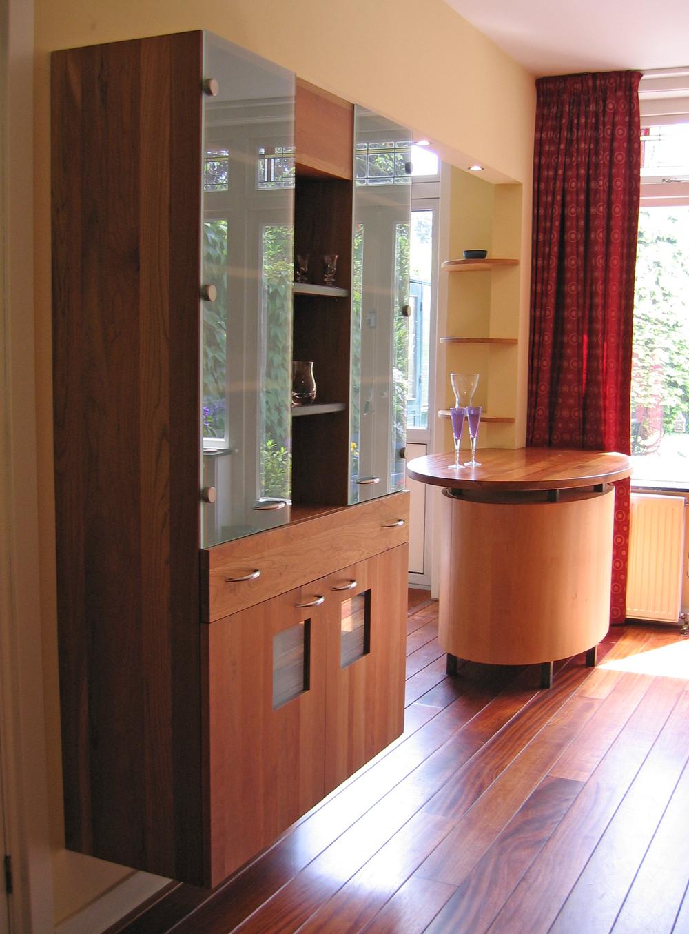Vrijstaande tafel, ronde planchetten aan muur en zwevend opgehangen wandkast