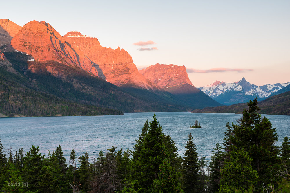 The rising sun illuminates the mountains lining St. Mary Lake, Wild Goose Island can also be seen.