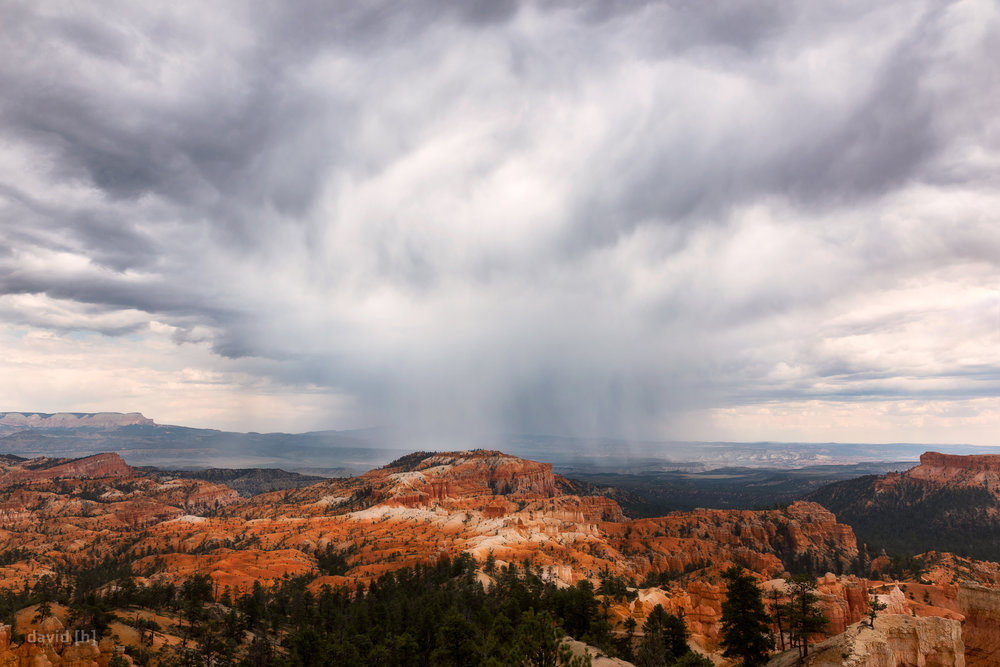 A storm cell twisting above Bryce Canyon and lashing the orange rock with some heavy rain.